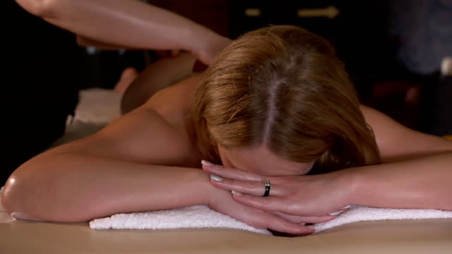 Spa massage. Aromatherapy oil massage. Woman lokking at the camera and smiling. Masseur doing aromatherapy oil massage on beautiful young healthy caucasian woman body in spa salon video