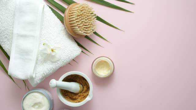 スパの静物画。ピンクの背景に白いタオルとトロピカルヤシの休暇 - 体 洗う点の映像素材/bロール