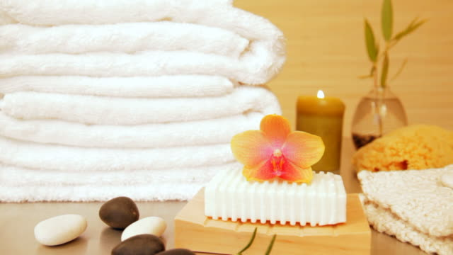 Spa still life of bar with soap orchid and towels