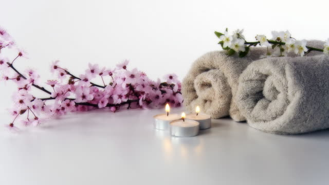 HD DOLLY: Spa Still Life HD1080p: DOLLY STUDIO shot of a spa still life in a high key technique. Towels, candles and beautiful spring blossoms on a white background. spa treatment stock videos & royalty-free footage