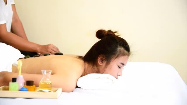 spa stein massage asiatische schönheit frau therapie entspannen behandlung im spa-salon.  junge ethnische glück schönheit frau liegen spa bett hautpflege bio massage körper regenerative. spa-salon resort therapeut. - la stone therapie stock-videos und b-roll-filmmaterial