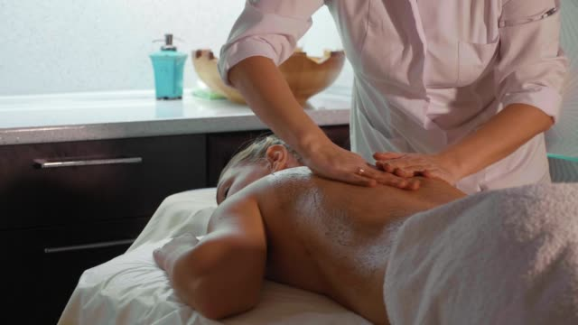 Spa therapist applying scrub on young woman back at luxury beauty salon. video