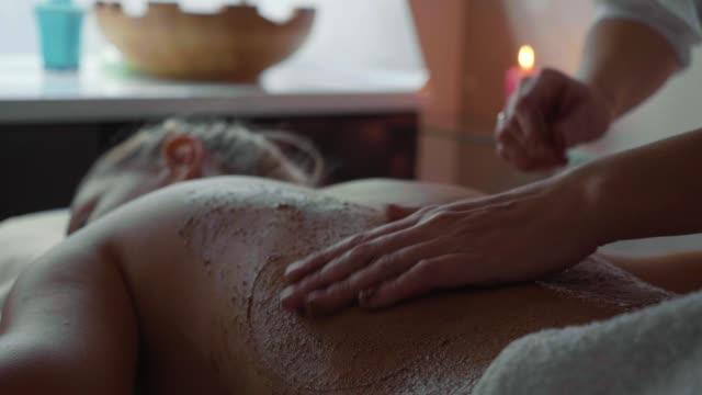 vidéos et rushes de thérapeute de spa appliquer le gommage sur la jeune femme au salon de beauté de luxe. - soin spa