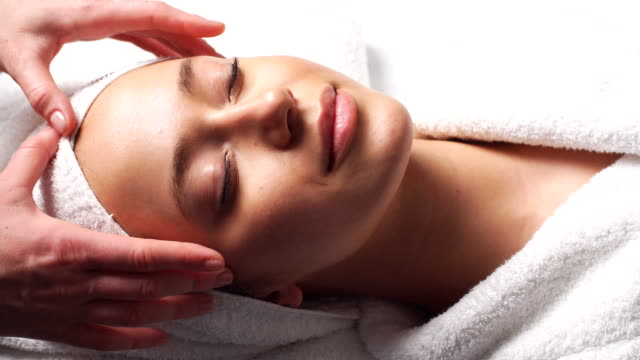 Spa woman facial Massage. Face Massage in beauty spa salon. Female enjoying relaxing face massage in cosmetology spa centre. Body care, skin care, wellness, beauty treatment video