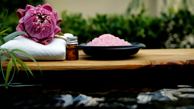 vídeos de stock e filmes b-roll de spa zen relaxation with pink waterlily lotus and pink himalayan salt on water slowmotion flowing , keep and calm meditation , work life balance concept - fitoterapia