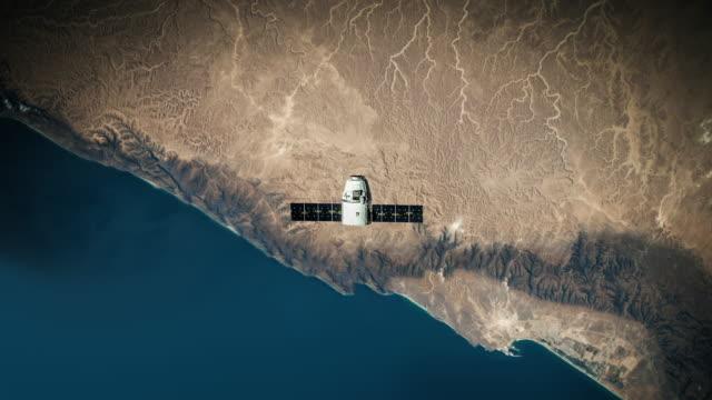 космическая капсула, вращающаяся над землей 4k - вид со спутника стоковые видео и кадры b-roll