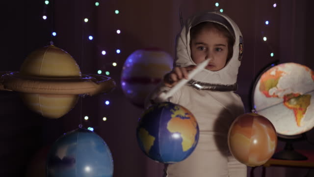 space travel game inspiration spaceship. little kid girl astronaut launching toy rocket from spaceport through planets. child dreamer playing with toy space rocket flying among planets. slow motion. - wyobraźnia filmów i materiałów b-roll