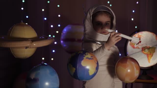 space travel spiel inspiration raumschiff. little kid girl astronaut start spielzeugrakete von spaceport durch planeten. kind träumer spielen mit spielzeug-raum rakete fliegen zwischen planeten. zeitlupe. - raumanzug stock-videos und b-roll-filmmaterial