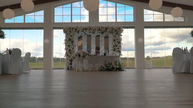 vidéos et rushes de salle spacieuse avec tables décorées pour la célébration de mariage - lieu sportif