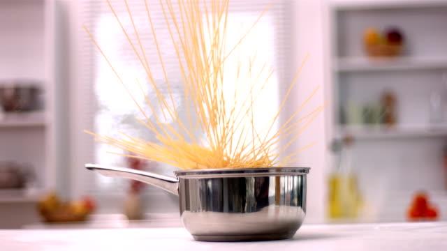 vidéos et rushes de spaghetti tomber dans une casserole de cuisine - spaghetti renversé