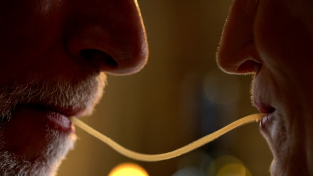 spaghetti kiss of senior couple, passion in spite of years, together forever - data scritta video stock e b–roll