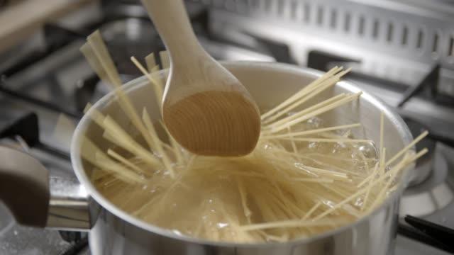 spaghetti pastas kochen zeitlupe 4k - pasta stock-videos und b-roll-filmmaterial