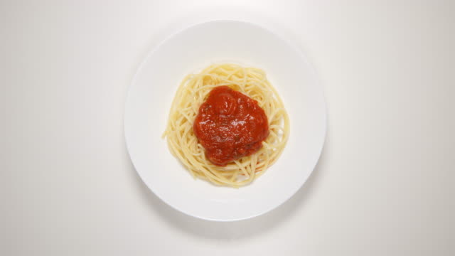 top view: spaghetti with sauce on a white dish - put, eat (stop motion) - тарелки стоковые видео и кадры b-roll
