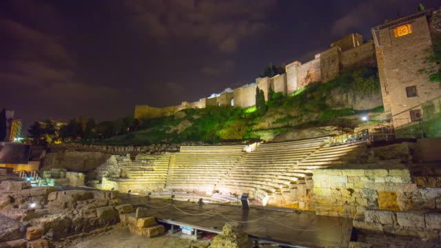 vídeos de stock, filmes e b-roll de espanha málaga luz noturna antigo coliseu parte vista do castelo de 4 k lapso de tempo - monumento
