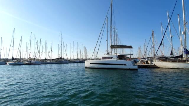 vídeos y material grabado en eventos de stock de barcos españoles en marina valencia. vista de los yates en el puerto desde un barco de recreo. club náutico en españa - anclado