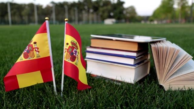 stockvideo's en b-roll-footage met spaanse taal en onderwijs. vlag van spanje en boeken over het gras. - literatuur