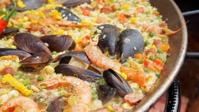 Spanish paella with yellow rice, shrimps and mussels cooking at the food market. Street food festival. Traditional spanish food. Rice with seafood boiling close up video