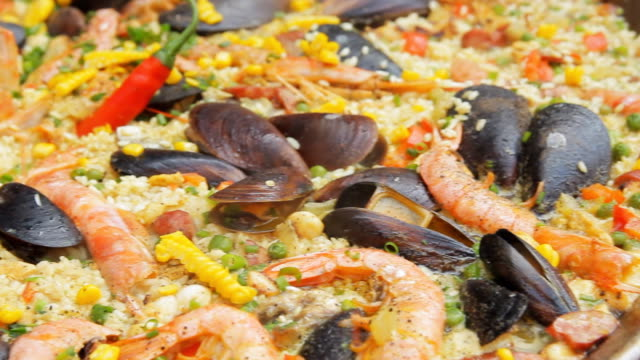 Spanish paella with yellow rice, shrimps and mussels cooking at the food market. Panning camera. Street food festival. Traditional spanish food. Rice with seafood boiling close up