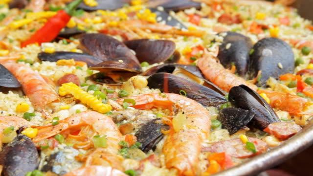 Paella espagnole avec riz jaune, crevettes et moules de cuisson au marché alimentaire. Caméra panoramique. Festival de la gastronomie de rue. Riz aux fruits de mer bouillante se bouchent. Cuisine traditionnelle espagnole - Vidéo