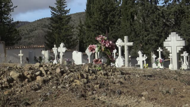 4K Spanish rural graveyard with headstone, old white cross and cypress tree