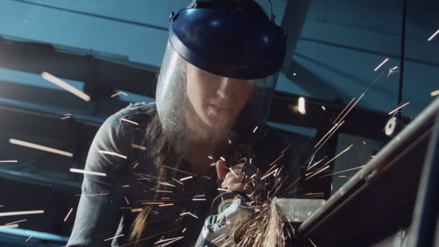vídeos de stock e filmes b-roll de spark shower from woman using angle grinder - moedor