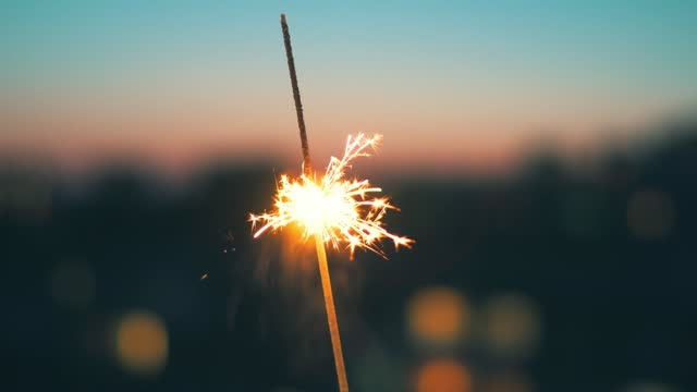 Sparkle Bengali fire bright burning wand of against the background of bokeh of evening city at sunset of the day. Christmas pattern. Orange lights fall on all sides. Happy New Year. Copy space