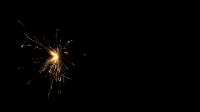 Sparkler Sparkler on crushed black background. Flame position constant for seamless loop of middle section of clip. firework explosive material stock videos & royalty-free footage