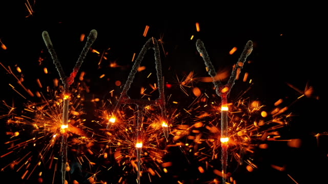 SLO MO LD Sparklers shaped as the exclamation 'YAY' emitting sparks