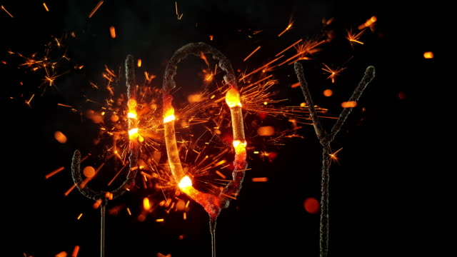 SLO MO LD Sparklers shaped as the word 'JOY' emitting sparks