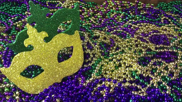Sparkling colorful carnival mask on pile of Mardi Gras beads