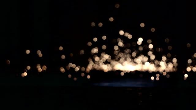 funkelnde Partikel auf den Boden fallen und explodieren im Dunkeln – Video