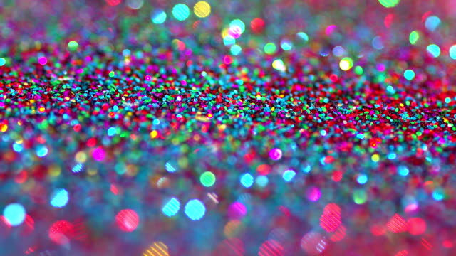 sparkly glitter background in bright colors. great party background texture - посыпать стоковые видео и кадры b-roll