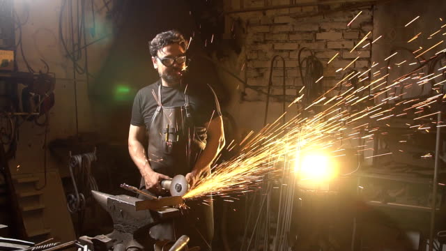 Sparks during cutting of metal angle grinder. blacksmith working in a workshop with metal. Worker using industrial grinder. slow motion blacksmith forges on the anvil. brutal man working at the forge with metal blacksmith stock videos & royalty-free footage