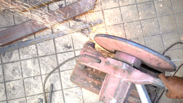Sparks during cutting of metal angle grinder. blacksmith working in a workshop  with metal. Worker using industrial grinder. slow motion video