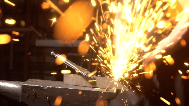 Sparks flying at the camera. A man working angular grinding machine. Blacksmith working with metal. Slow motion video