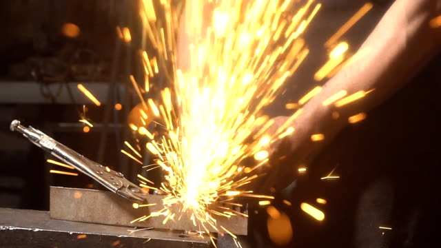 Sparks flying at the camera. Man working angular grinding machine. Slow motion video