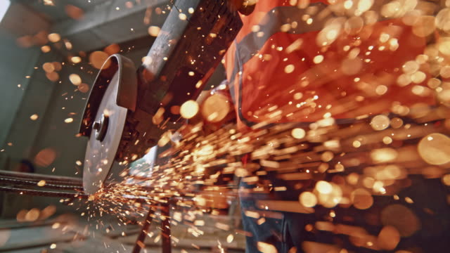 vídeos de stock e filmes b-roll de slo mo sparks flying from an angle grinder towards the camera lens - moedor