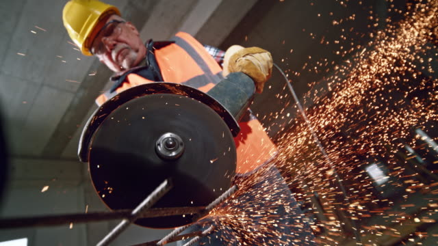 SLO MO LD Sparks flying from an angle grinder Slow motion wide low angle locked down shot of a senior male construction worker holding an angle grinder and cutting a steel mesh while sparks are flying in the air. Shot in Slovenia. grinder industrial equipment stock videos & royalty-free footage