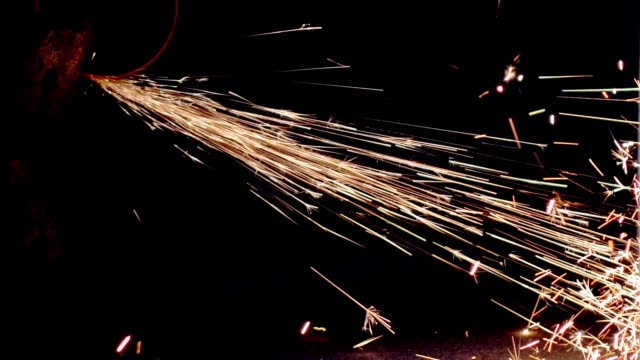 vídeos de stock e filmes b-roll de sparks flying from angle grinder when cutting and grinding metal slow motion - moedor