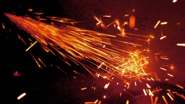 sparks flying from angle grinder when cutting and grinding metal slow motion - rettificatrice video stock e b–roll