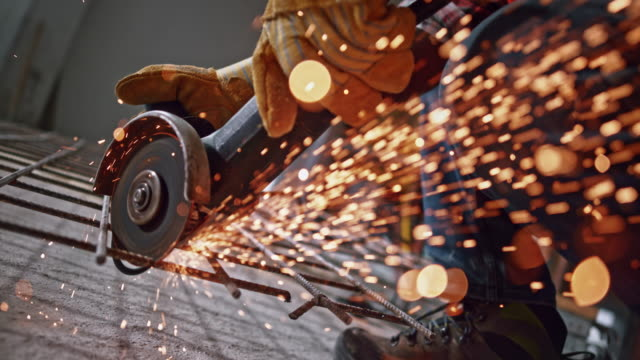 SLO MO LD Sparks flying from the disc of the angle grinder cutting steel Slow motion medium low angle locked down shot of sparks flying from the angle grinder being used to cut a steel mesh. Shot in Slovenia. grinder industrial equipment stock videos & royalty-free footage