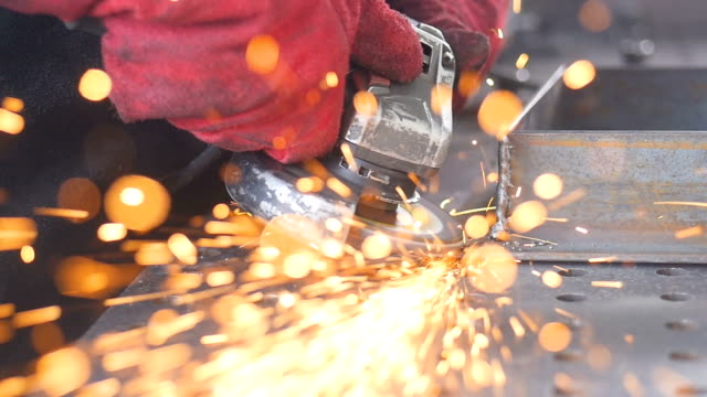 sparks from angle grinder cut metal fly in to camera lens. slow motion. - rettificatrice video stock e b–roll