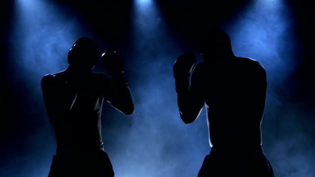 Sparring of two boxers in the studio. Silhouette, smoke video