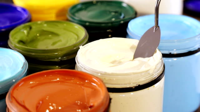 spatula is gaining acrylic paint in ivory from the banks. preparing to draw. - tavolozza video stock e b–roll