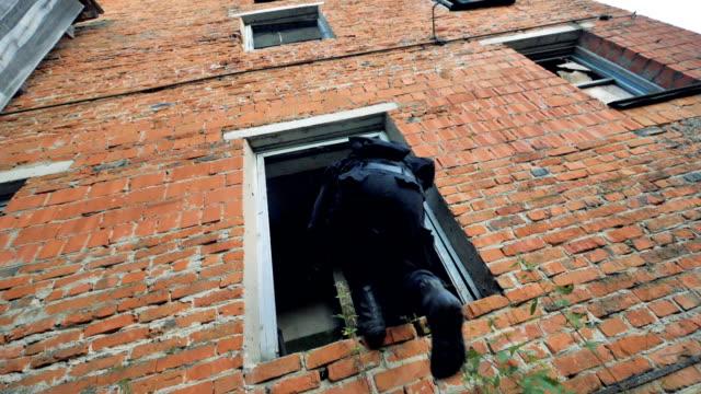 特殊部隊の軍人は、れんが造りの建物の位置をオーバーランします。 - こっそり点の映像素材/bロール