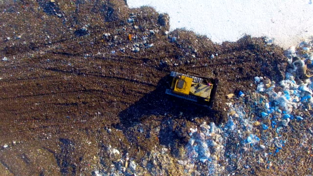 Special machinery working at the garbage dump. Landfill directly from above. Aerial shot.