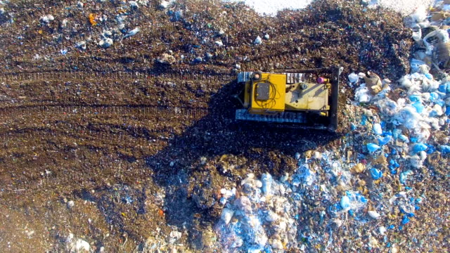 4K. Special machinery working at the garbage dump. Landfill directly from above. Aerial shot.