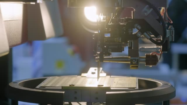 a special modern machine installs a silicon microprocessor on the board. the robot manipulator solders the chip contacts to the matrix. modern computer technology. - processore video stock e b–roll
