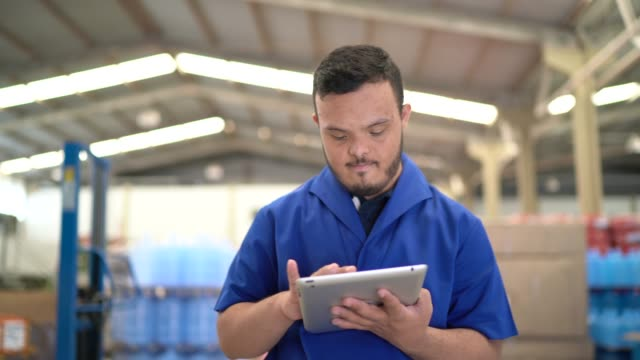 Special needs young man using digital tablet and working in industry