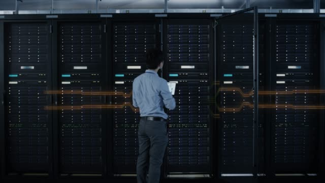 IT Specialist Activates Data Center Server Racks with a Touch Gesture. Animated Concept of Digitalization of Information: Network of Red Lines Spreading Symmetrically